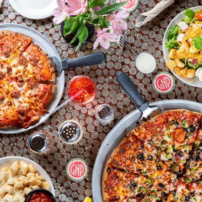 Top down shot of table full of food at Glass Nickel Pizza