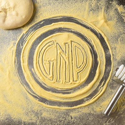 Glass Nickel Pizza Logo drawn in Pizza Dough flour