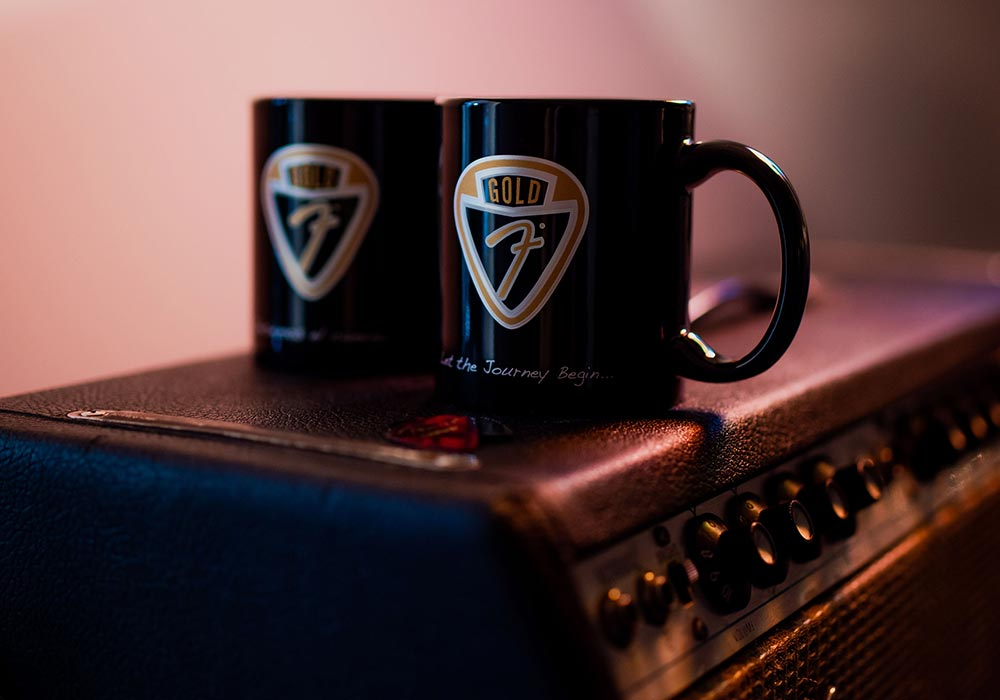 A set of mugs featuring the Fender Gold logo