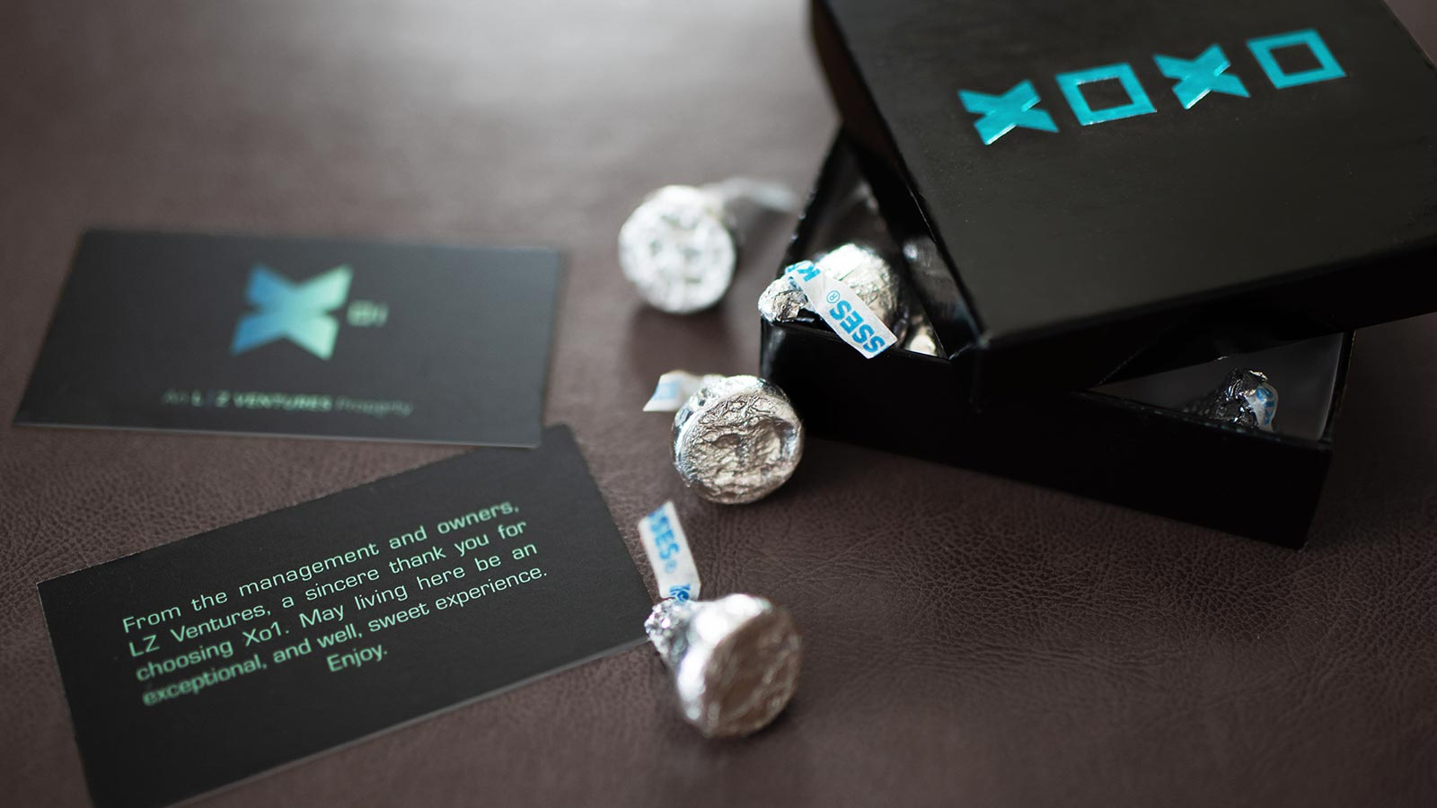 X01 branded welcome package containing a thank you card and candy
